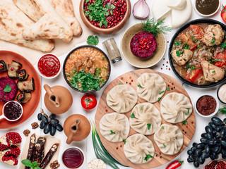 View from above of georgian cuisine on white wooden table. Traditional georgian cuisine and food - khinkali, kharcho, chahokhbili, phali, lobio and local sauces - tkemali, satsebeli, adzhika. Top view Fototapete