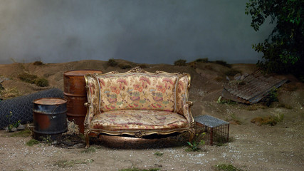 Gold settee next to rusty oil barrels