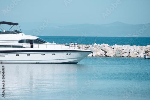 High speed boat, luxury yacht in dock in sea, blue sky on