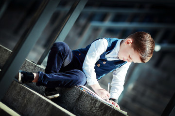 The younger fashionable boy draws in a notebook sitting on the steps.