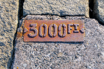 Metal sign (3000Ft) on Leith Harbour dike, Edinburgh, Scotland