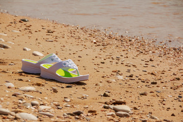 white sandals on the beach. Flipflops on a sandy ocean beach - summer vacation concept. Beach fashion. Female summer casual shoes. Copy space