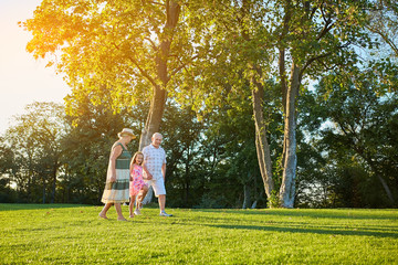 Seniors with grandchild walking outdoors. People, green grass and trees.