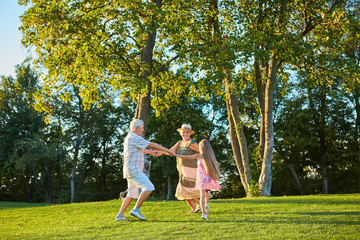 Girl with grandparents dancing outdoors. Roundelay on green grass. Energy of generations.