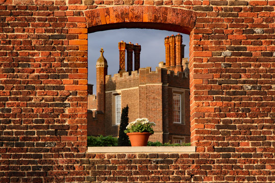 Hampton Court Palace seen through a window in a bright red brick wall with a pot plant suggestive of the upcoming flower show. Copy space on image.