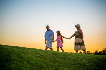 Girl and grandparents, sunset sky. Seniors with grandchild holding hands.