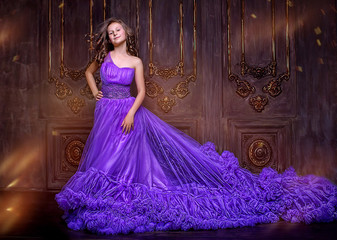 Portrait of lovely young girl in purple long dress