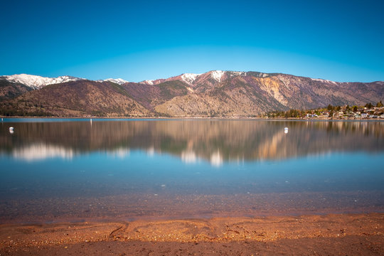 A long exposure of Lake Chelan shows off vibrant blue skies and reflections of the snowcapped mountains