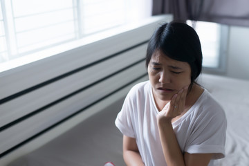 Young asian woman have a toothache,Female feeling exhausted and painful