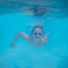 Pre-teen Boy Swimming Underwater in Pool with Smile