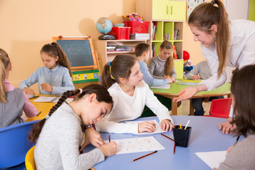 Woman teacher helping to group of pupils drawing