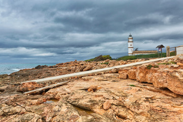 Island scenery with rocks and sea in gloomy weather, lighthouse