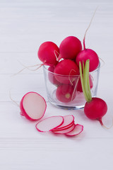 Sliced and whole radishes on wooden background. Chopped radish near radishes in glass container.