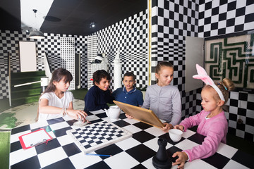 kids discuss the game in the chess quest room