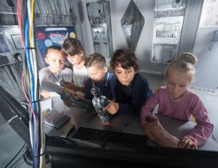 children discuss the game  in bunker quest room