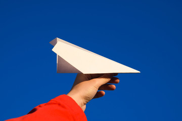White paper airplane in hand against the sky. A symbol of freedom on the Internet.