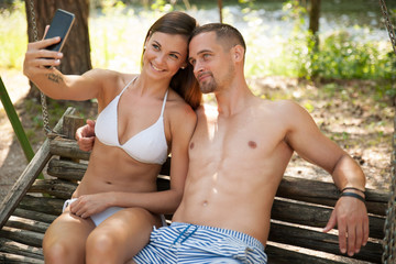 Active young couple taking selfie on a bench in park near river