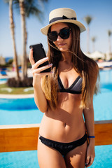 Happy woman in straw hat and sunglasses relaxing near swimming pool using her mobile phone