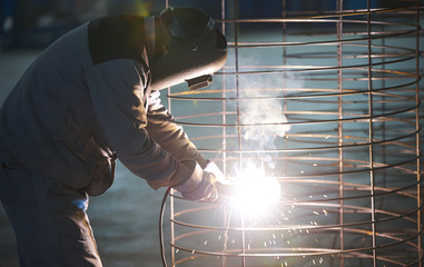 Welder man welds at the factory. Industrial Worker welder welding steel structure for concrete pipe. Industry manufacturing concept