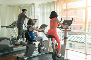 Group of friends athletes doing exercises together on gym machines in fitness center. Workout, sport, lifestyle concept.