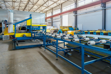Thermal insulation sandwich panel production line. Roller conveyor, insulation panel assembly machine in workshop