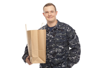Young man in navy uniform with grocery store paper bag