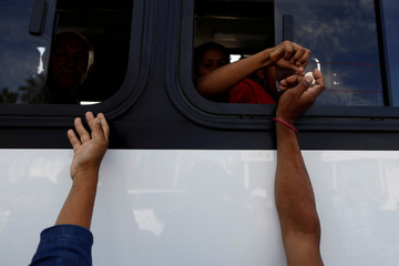 A group of Central American migrants, moving in a caravan through Mexico, ask for money to get on a microbus to the office of Mexico's National Institute of Migration, in Hermosillo