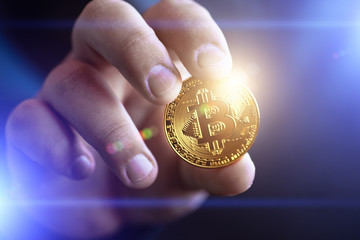 Cryptocurrency golden bitcoin coin in man hand - symbol of crypto currency - electronic virtual money for web banking