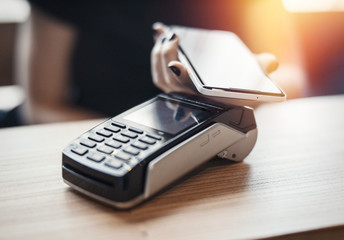 Young woman pays via payment terminal and mobile phone.