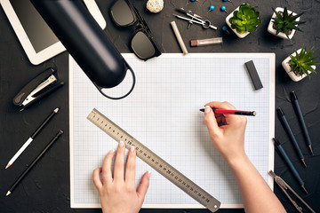 Office desk background hand with pen writing construction project ideas concept, With tablet, drawing equipment and lamp. View from above