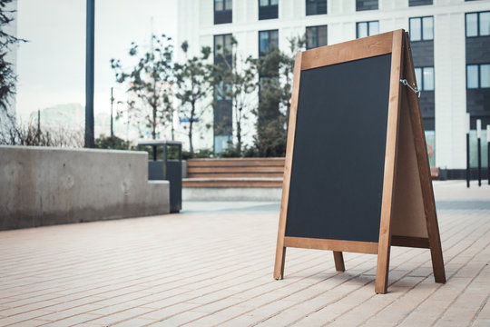 Blank Sandwich Board at the Street Near skyscrapers. Business Center, Commercial Center, Downtown.  Copy Space, Empty Space for Advertising