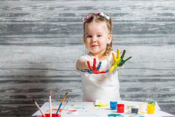 little girl draws. Hands of a girl in paint
