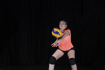 Young woman volleyball player isolated on black background