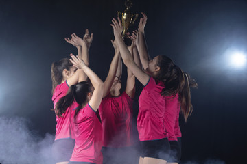 Young Female volleyball team celebrating victory in game