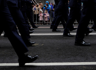 People watch a contingent march past during an Anzac Day parade in Sydney