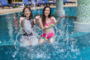 two young woman friends splashing water in swimming pool