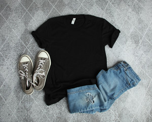 Mockup Flat Lay of Black T shirt with gray canvas shoes and ripped jeans on a gray background