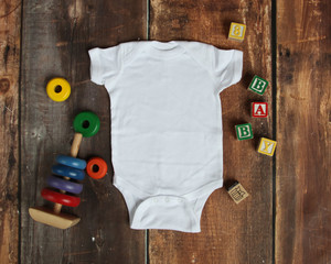 Mockup Flat Lay of white baby bodysuit shirt on rustic wood background with wooden blocks and baby toys