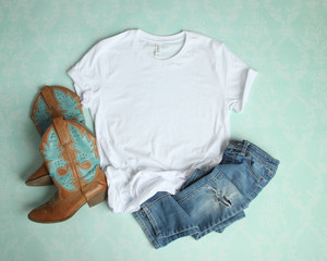 Mockup Flat Lay of White Tee shirt with cowboy boots and ripped jeans on an aqua blue background