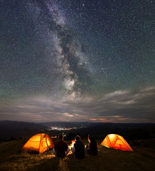 Back view silhouette team sitting near campfire beside two orange tents at night under wonderfull sky with stars and Milky way on background of mountains and luminous town. Concept of a night camping