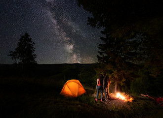 Spoed Fotobehang Kamperen Rear view of young couple tourists enjoying the starry sky with a bright Milky way under the mighty trees near the campfire and orange illuminated tent in mountains. Romantic night camping near forest