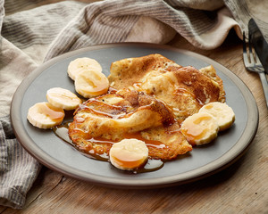 Crepes with banana and caramel sauce on wooden desk
