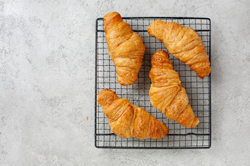 Croissants on a cooling rack on textured gray background, top view. Copy space.