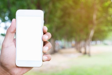 close up people hand holding display white mobile smart phone with blank of empty white screen on outdoor public parks green tree background.
