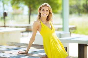 Attractive young blonde Caucasian woman in thin yellow sun dress posing outside on wooden table