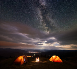 Camping illuminated orange tents on the top of mountain at night under starry sky and milky way on the background of the luminous town which is in the valley. Between the tents lit a bonfire