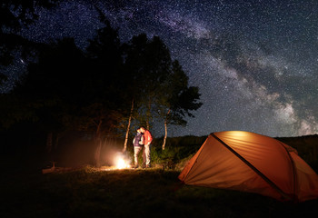 Guy and girl hikers having a rest by the campfire under a bright starry sky which is visible Milky way near the orange tent and trees. Romantic camping near the forest in the mountains