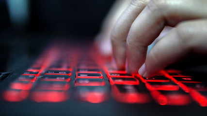 Unrecognized person typing on laptop computer red keyboard in dark, cinematic color graded footage