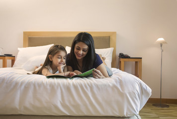 Mother and daughter lying on bed looking at picture book