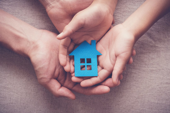 Adult and child hands holding paper house, family home, homeless shelter, foster home care, family day care, social distancing, stay at home concept